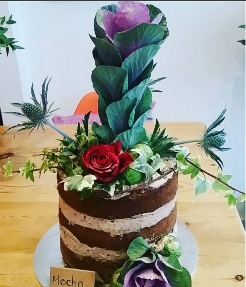 triple layer cake with cabbage plant and roses on top